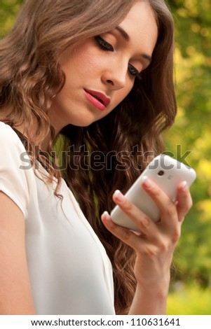 Young caucasian woman with a cell phone in park - stock photo