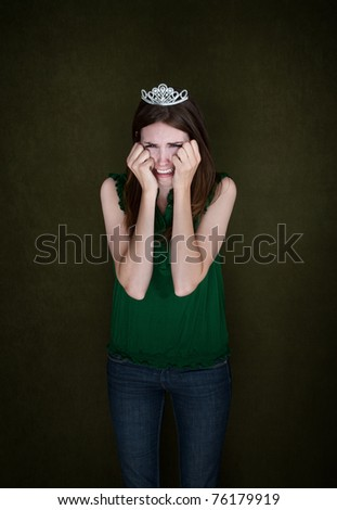 Young Caucasian woman with a tiara weeps - stock photo