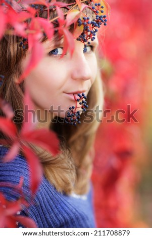 Young Caucasian woman with blue eyes in crown of red autumn leaves and blue berries of wild grape
