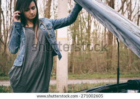 Young caucasian woman with brown hair under the hood of her car break down - stock photo
