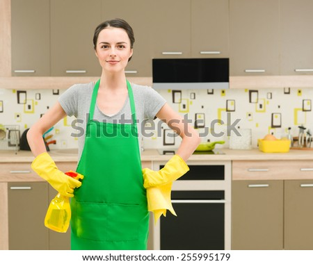 young caucasian woman with cleaning workwear and supplies standing in kitchen, getting ready for spring cleaning - stock photo