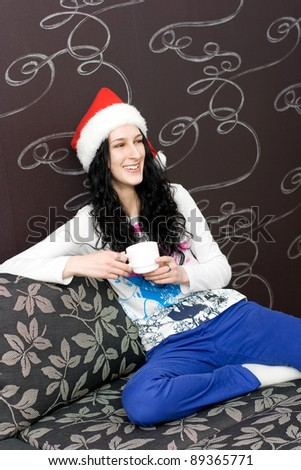 Young caucasian woman with cup of tea in santa hat - stock photo