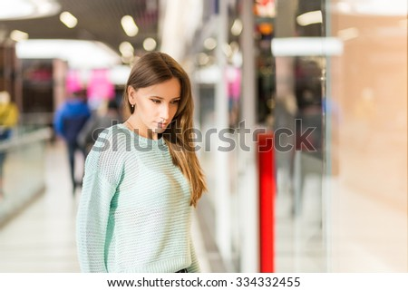 Young caucasian woman with dark brown hair looking through window in the mall. Window shopping background