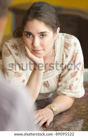 Young Caucasian woman with hand on chin in kitchen - stock photo