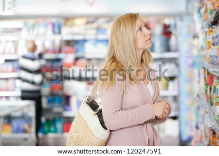 Young Caucasian woman with handbag shopping at supermarket - stock photo