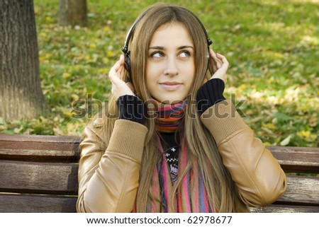 Young Caucasian woman with headphones in autumn park sitting on a wooden bench. Autumn around a lot of colorful foliage - stock photo