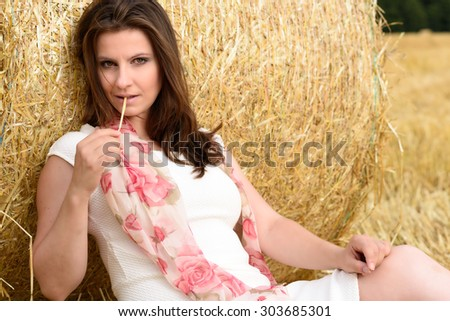 Young Caucasian woman with long brown hair is sitting in a fresh mowed corn field -  leaning against a bale of straw - stock photo