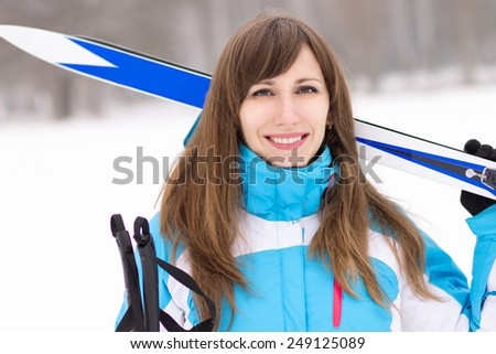 Young caucasian woman with ski at snowy winter day. Happy smiling girl going skiing - stock photo
