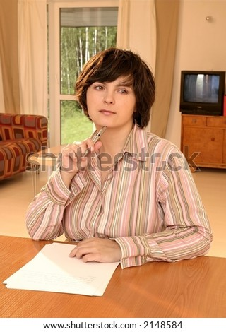 Young caucasian woman writing on paper in her room.