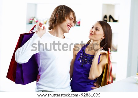 Young caucausian couple with bags doing shopping together - stock photo