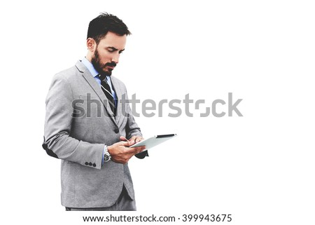 Young CEO or businessman is reading news on web page via portable touch pad, while is standing against clear wall background with copy space for your advertising text message or promotional content - stock photo
