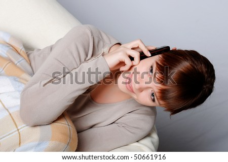 Young charming brunette in a gray jacket resting on the sofa - stock photo