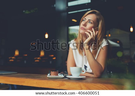 Young charming European woman calling with cell telephone during morning breakfast in coffee shop, beautiful female having talking conversation with mobile phone while relaxing during work break - stock photo