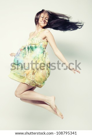Young charming female in chiffon dress jumping over grey background
