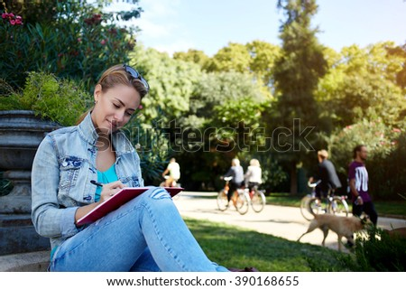 Young charming female is writing something in her diary while is relaxing in the fresh air during recreation time, woman student is preparing to college tuition while is sitting with notepad outside - stock photo