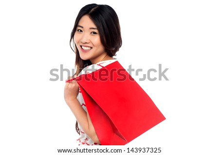 Young charming girl carrying shopping bag