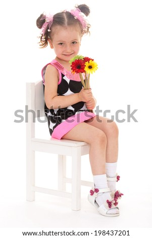 young charming girl with pigtails sitting on a white chair with a bouquet of flowers and smiling cheerfully. on a white background - stock photo