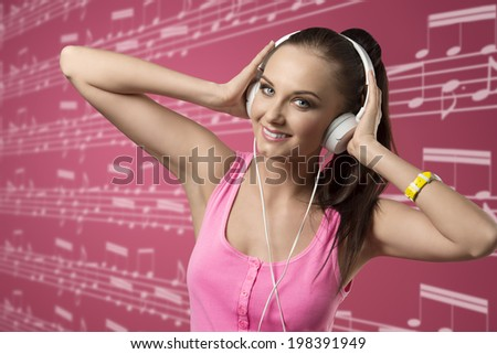 young charming girl with ponytail and pink singlet listening music with headphones, looking in camera and smiling  - stock photo