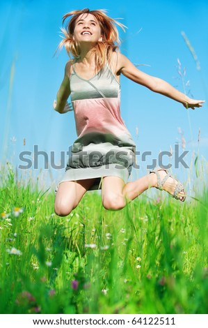 Young charming laughing woman in beautiful dress jumps against dark blue sky and green grass on meadow. - stock photo