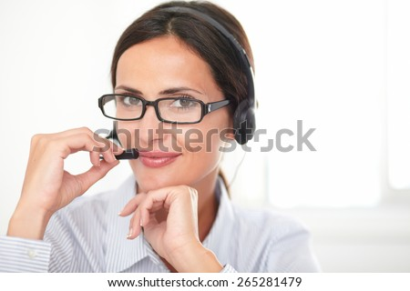 Young charming secretary in blue blouse speaking on the earphone while smiling and looking at you - stock photo