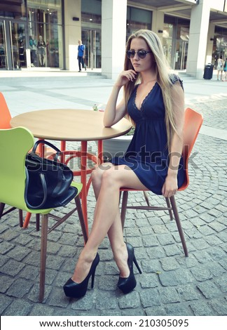 Young Charming Smiling Blond Woman Relaxing in Open-air Cafe. Urban Lifestyle. Image Toned. - stock photo