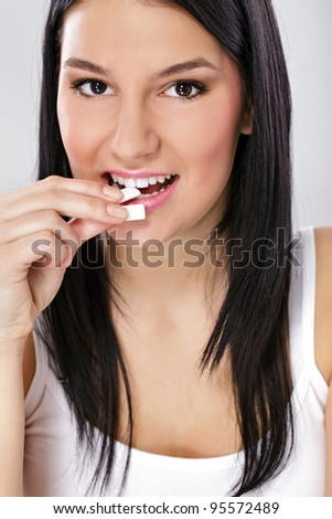 Young charming smiling dark-haired woman puts in mouth chewing gum - stock photo