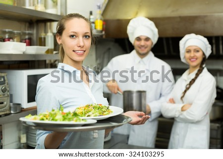 Young charming waitress holding plates with prepared meal at restaurant kitchen