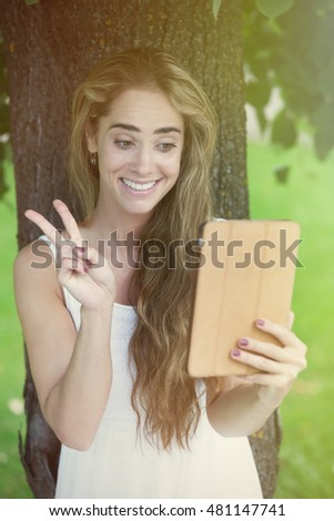 Young charming woman charming under the tree via table pc