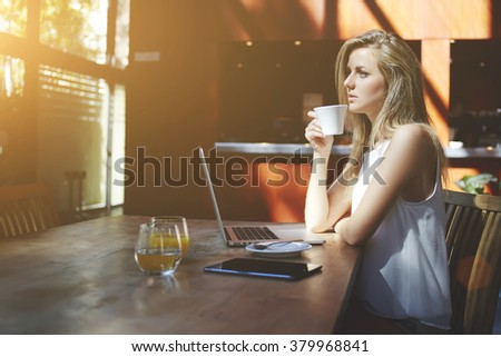 Young charming woman dreaming about something while enjoying good tea after work on laptop computer, thoughtful hipster girl drinking coffee while waiting answer on her e-mail on portable net-book - stock photo