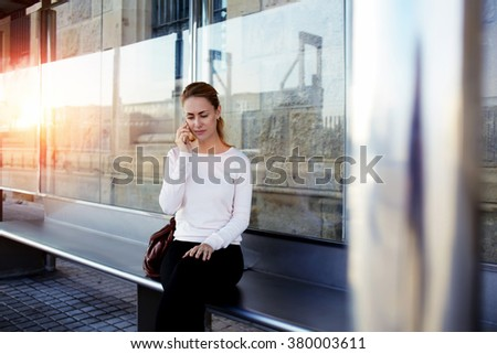 Young charming woman having bad conversation with her boyfriend while she waiting for a car on a station, attractive female calling on smart phone to her friend while sitting alone on a bus stop  - stock photo