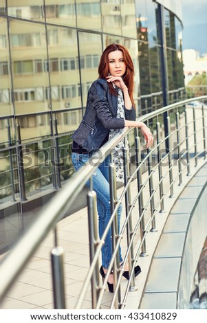 Young charming woman in blue jeans, black leather jacket and with stylish scarf, standing. Outdoors. Full - length.  - stock photo