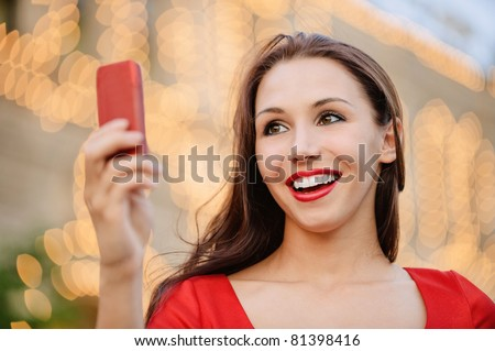 Young charming woman in red dress reads text message on mobile phone and laughs. - stock photo
