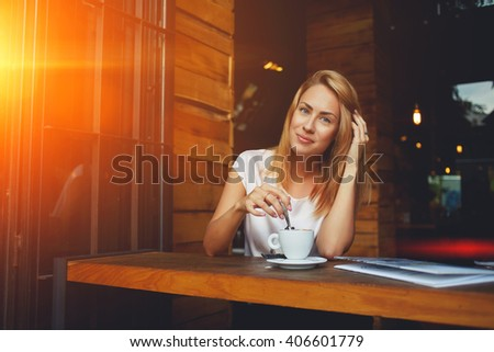 Young charming woman posing while sitting in cafe during coffee break, attractive European female enjoying rest during recreation time, beautiful lady relaxing in bar after walking in the fresh air  - stock photo