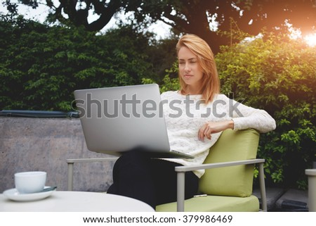 Young charming woman watching video on laptop computer while relaxing in sidewalk cafe during coffee break, beautiful female reading fashion news on net-book while sitting in restaurant outdoors - stock photo