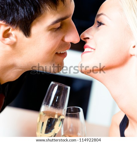 Young cheerful amorous kissing couple with champagne on romantic date or celebrating at restaurant