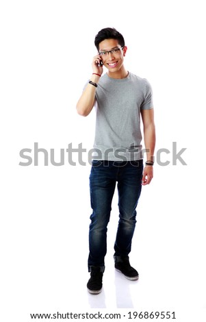 Young cheerful asian man talking on the phone over white background - stock photo