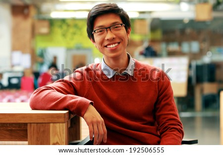Young cheerful asian student sitting at the table - stock photo