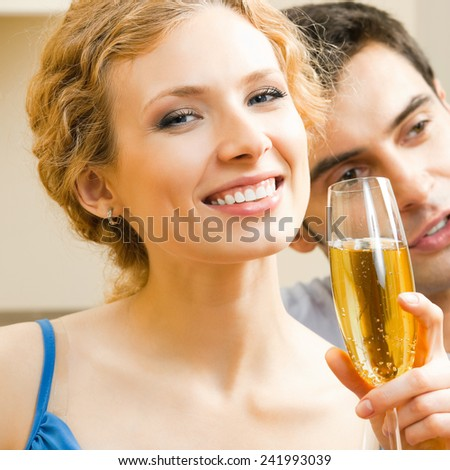 Young cheerful attractive couple celebrating with champagne - stock photo