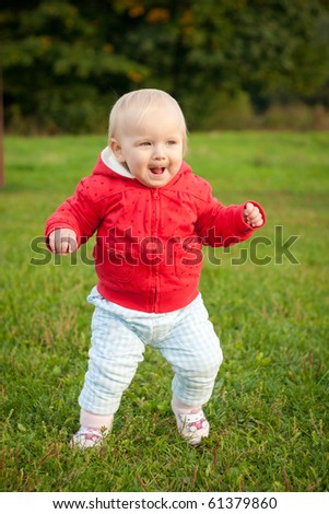 young cheerful baby running on the grass in park - stock photo