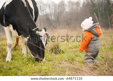 young cheerful baby stay near feeding cow - stock photo