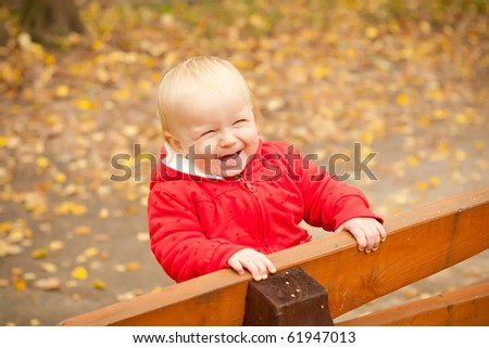young cheerful baby stay on wood bench in park forest and smile - stock photo