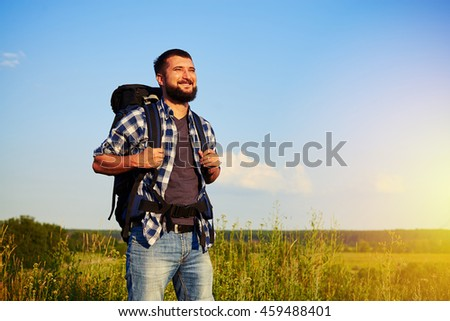 Young cheerful bearded man in casual clothes with rucksack is standing and smiling in the field enjoying the beauty of landscape - stock photo
