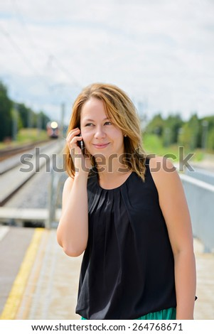 Young cheerful beautiful female in black top talking on mobile phone - stock photo