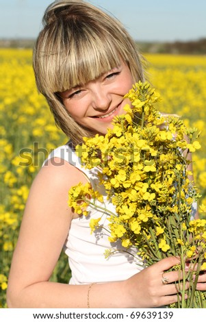 young cheerful beautiful woman on blooming field in summer - stock photo