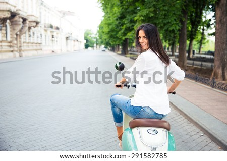 Young cheerful beautiful woman riding a scooter and looking back at camera - stock photo