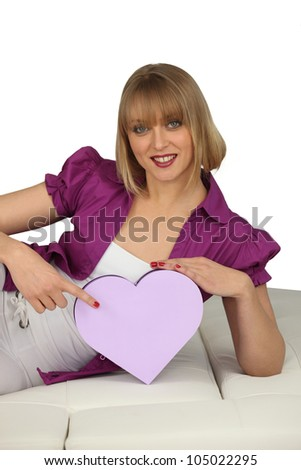young cheerful blonde on divan with box in shape of heart - stock photo