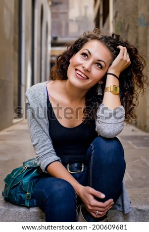 Young cheerful brunette girl in casual clothes in urban style