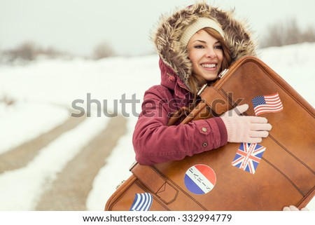 Young cheerful brunette holding suitcase and standing on the snow next to the road - stock photo