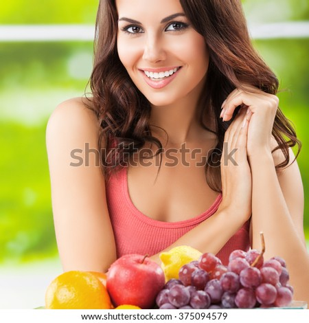 Young cheerful brunette woman with plate of fruits. Healthy eating, beauty and dieting concept. - stock photo
