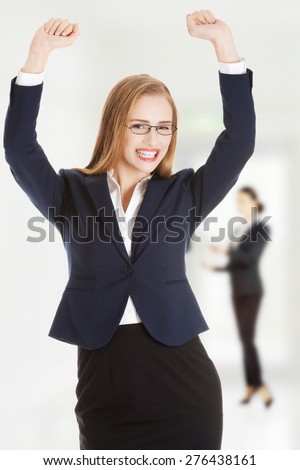 Young cheerful business woman making fists.